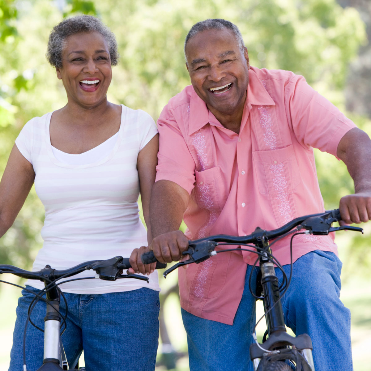An older african american woman and man laughing having fun while riding their bicycles