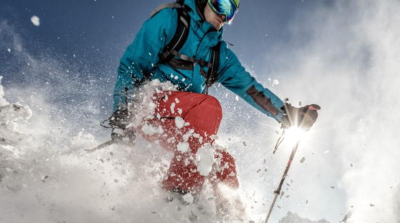 Man dressed in snow gear skiing