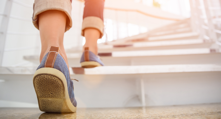 Closeup of a persons feet wearing sneakers about to walk up a long flight of stairs