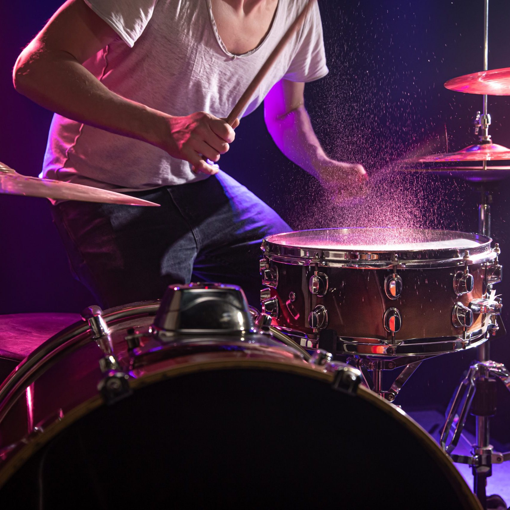 The drummer plays the drums. Beautiful blue and red background, with rays of light. Beautiful special effects smoke and lighting. The process of playing a musical instrument. The concept of music. Close-up photo.
